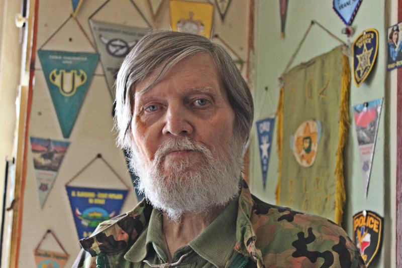 """Ladislav """"Frank"""" Nykl doma u stěny plné trampských vlajek. Foto: Martin Polák"""