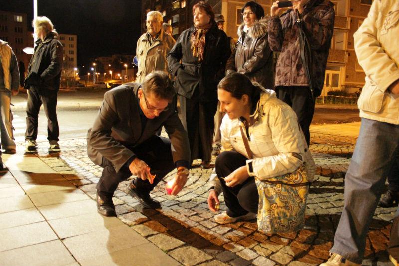 Místostarosta Luděk Soukup pomáhá zapalovat svíčku jedné z přítomných žen. Foto: M. Polák