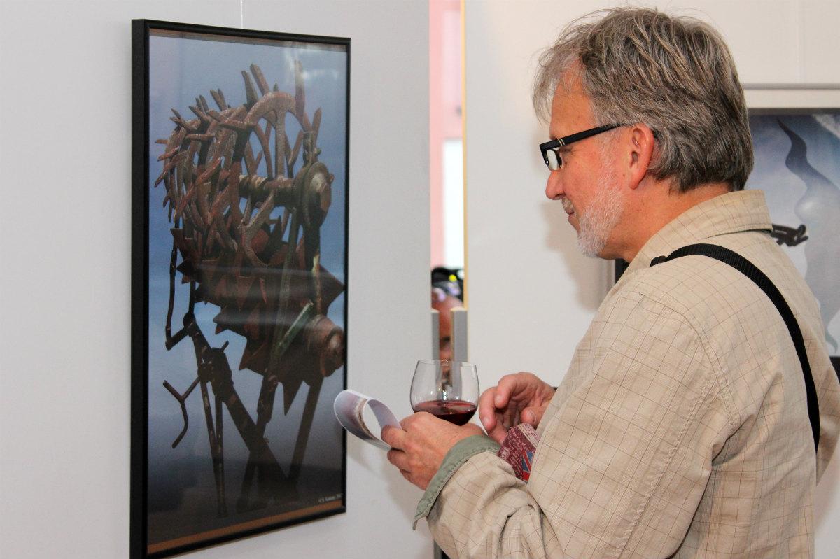 Návštěvník vernisáže si prohlíží fotografie Stanislava Koženého. Foto: Martin Polák