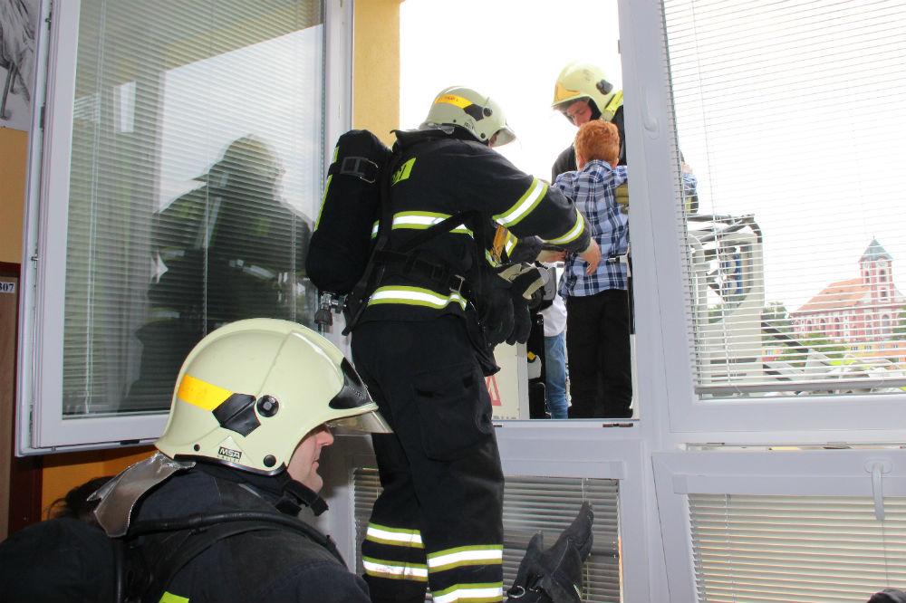 Hasiči pomáhají žákům na výsuvnou plošinu. Foto: Martin Polák