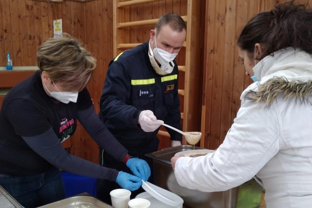 Hasiči rozdávají jídlo v chodovském evakuačním centru.